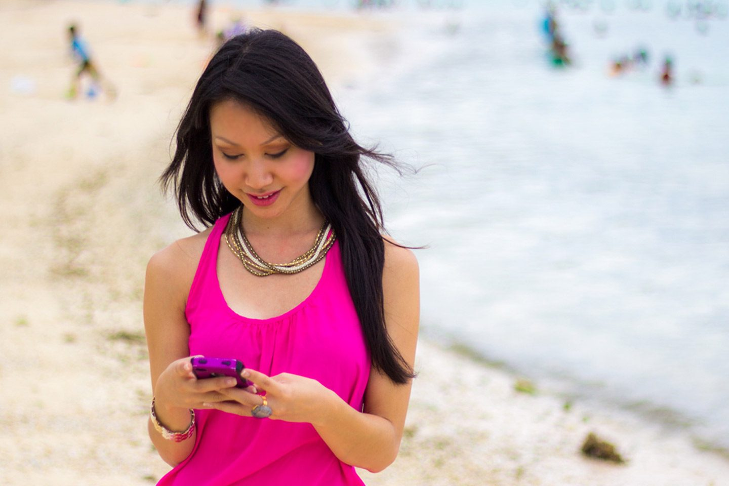 Asian woman holding cell phone and smiling on the beach